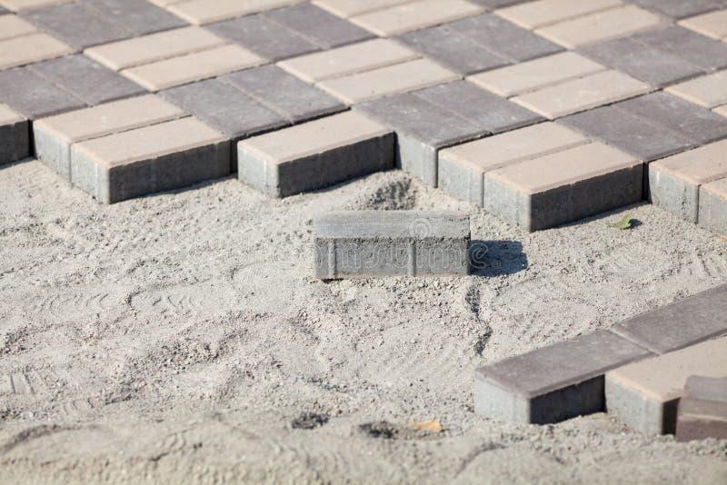 Серый цвет вымощая блоки - взгляд со стороны Новый тротуар с прямоугольными камнями на песочном балласте вымощая плитки в процесс стоковое фото rf