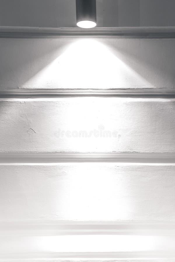 Серый цвет заштукатурил стена с лучом света от фары стоковые фото