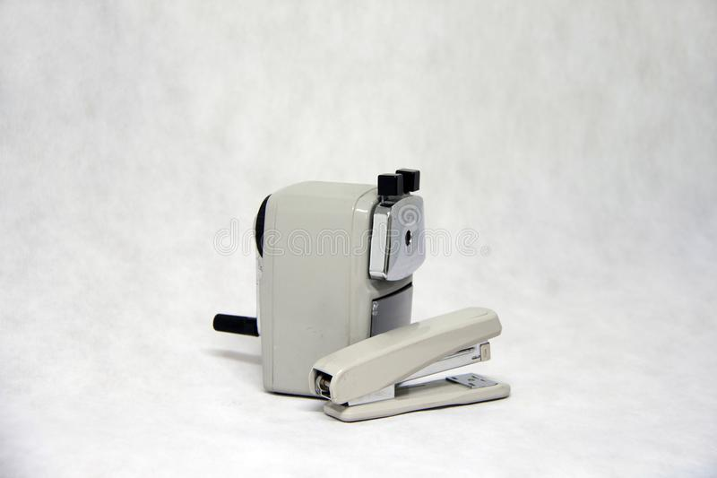 Серый цвет точилки для карандашей и сшивателя изолированных на белой предпосылке ткани стоковое фото