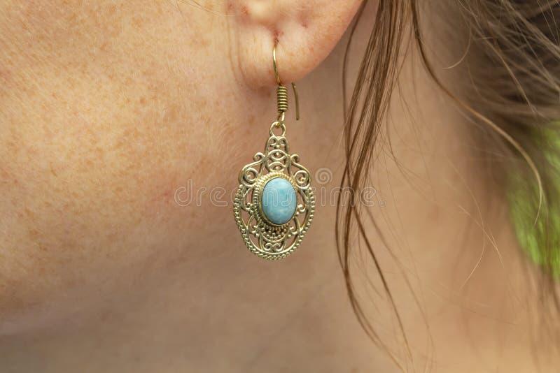 Серьга металла женщины нося латунная с минеральной драгоценной камнем стоковое изображение