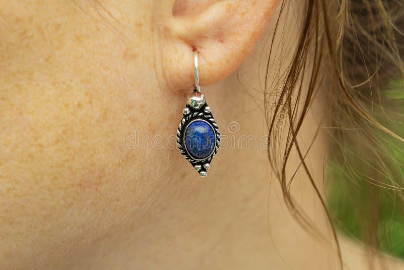 Серьга металла женщины нося латунная с минеральной драгоценной камнем стоковая фотография