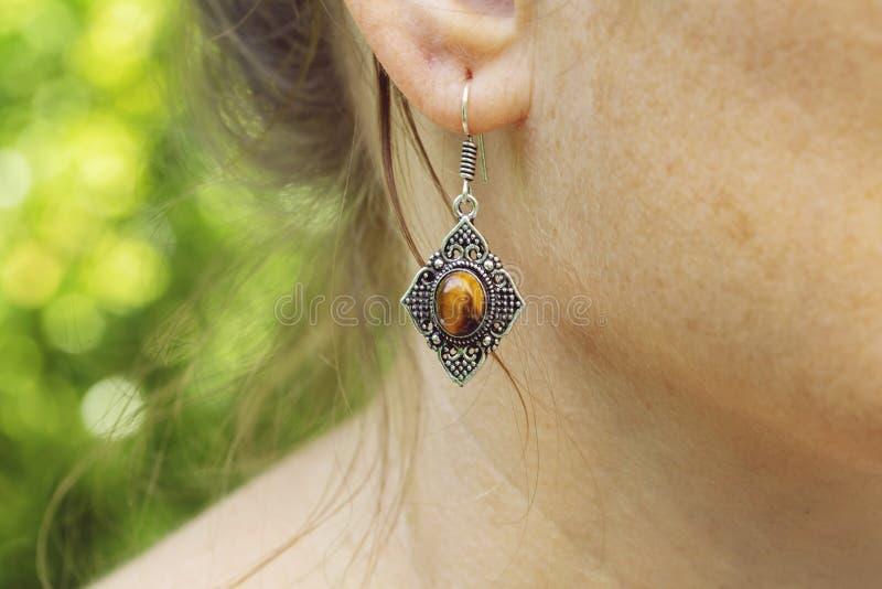 Серьга металла женщины нося латунная с минеральной драгоценной камнем стоковые изображения rf