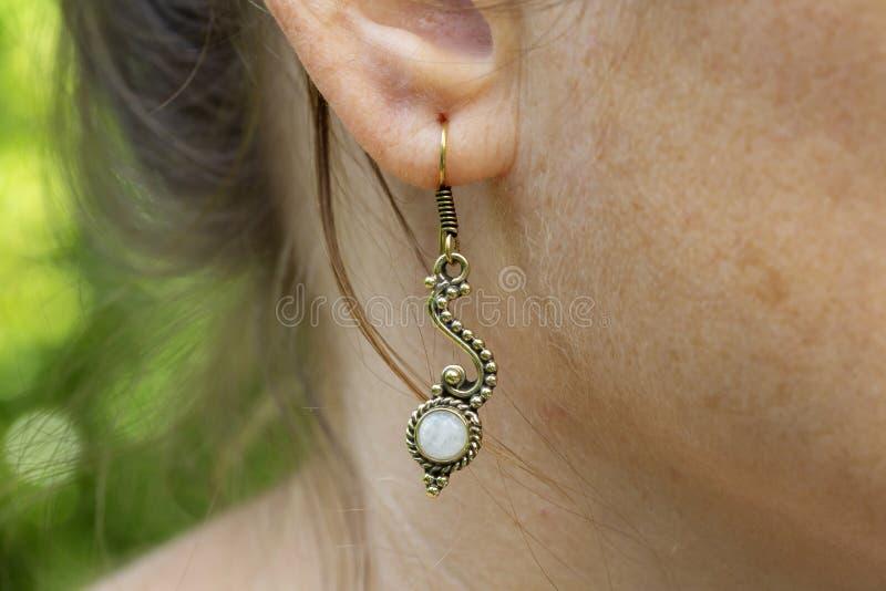 Серьга металла женщины нося латунная с минеральной драгоценной камнем стоковое фото rf