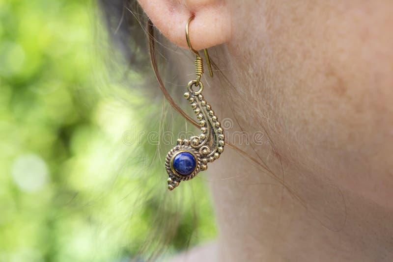 Серьга металла женщины нося латунная с минеральной драгоценной камнем стоковые фотографии rf