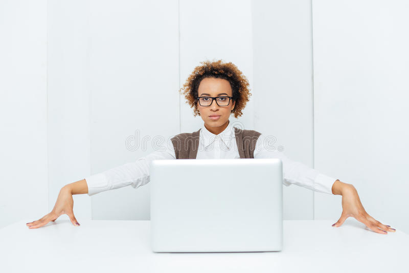 Серьезная Афро-американская коммерсантка сидя и представляя с компьтер-книжкой стоковые фотографии rf