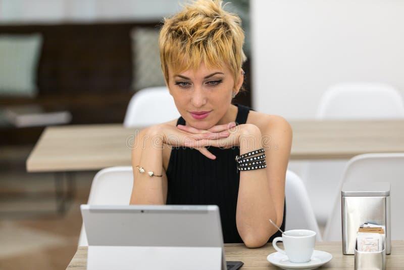 Серьезная бизнес-леди используя мобильный компьютер в баре стоковое фото rf