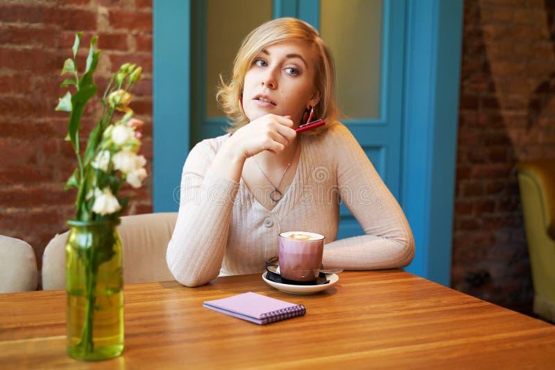 Серьезная внимательная девушка смотря камеру Кофе молодой женщины выпивая в кафе против кирпичной стены и голубой двери стоковые изображения
