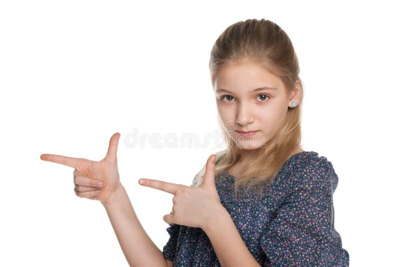Серьезная девушка показывает ей пальцы к стороне стоковые изображения