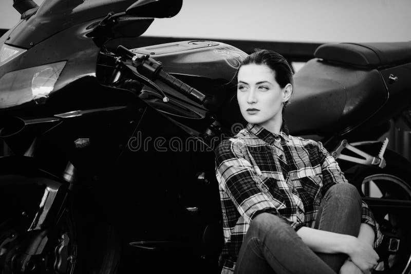 Серьезная женщина в рубашке на предпосылке мотоцикла, приглаживаемые волосы, черно-белые стоковое фото rf