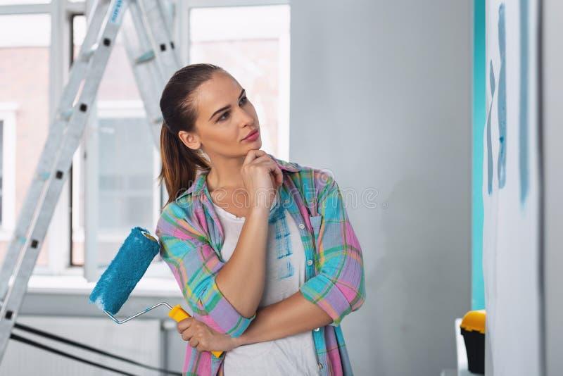 Серьезная женщина держа ролик для того чтобы покрасить стены стоковые изображения rf
