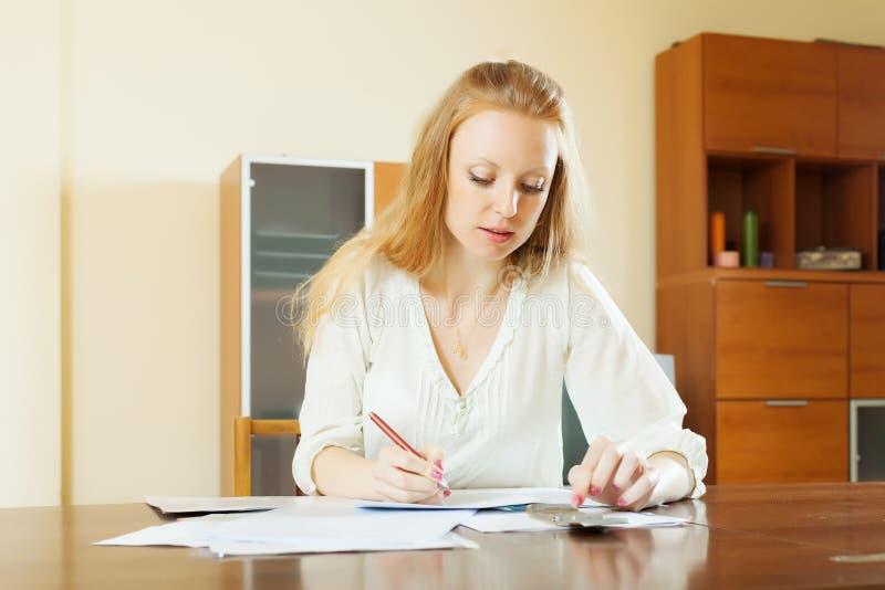 Серьезная женщина заполняет внутри финансовые документы стоковые фотографии rf