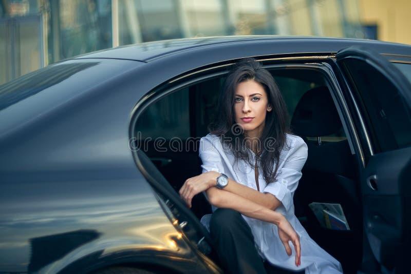Серьезная женщина сидя в автомобиле над современным фасадом офиса стоковые фотографии rf