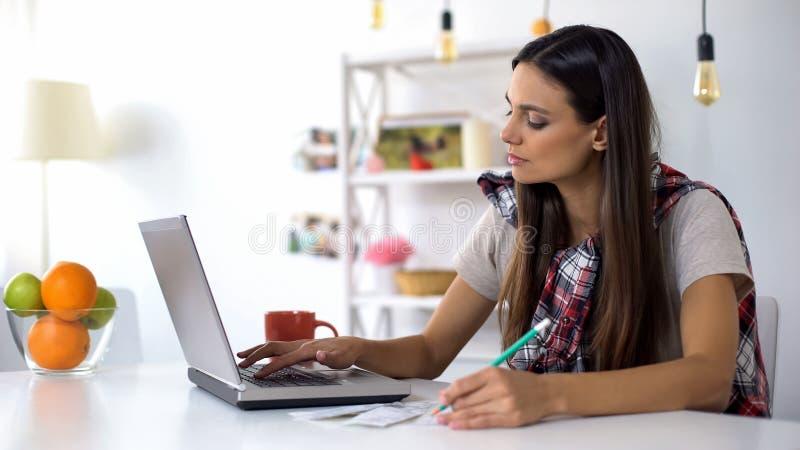 Серьезная женщина со счетами печатая на ноутбуке и высчитывая отечественные расходы стоковая фотография rf