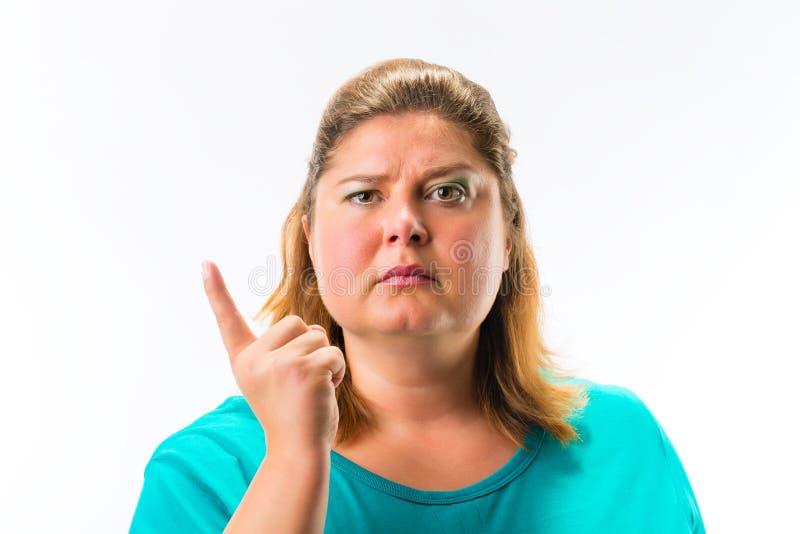 Серьезная женщина указывая ее палец вверх стоковое фото