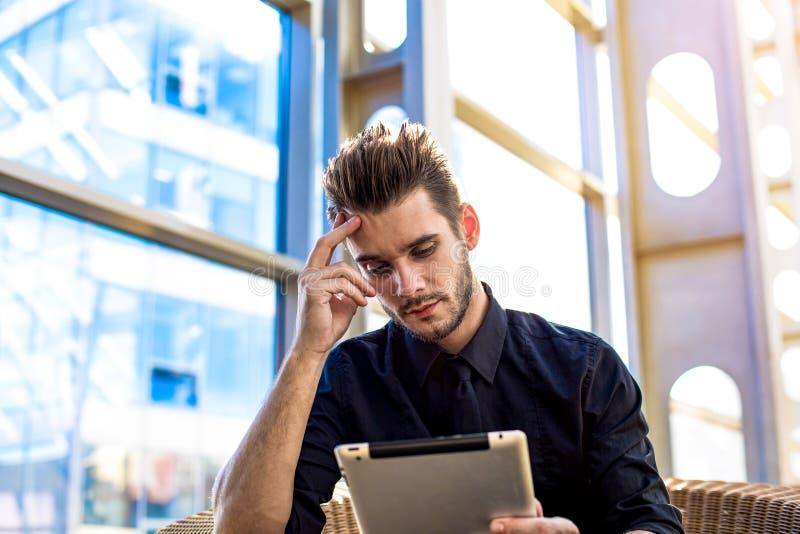 Серьезная зверская сводка чтения руководителя человека на цифровом планшете перед интервью стоковое фото rf