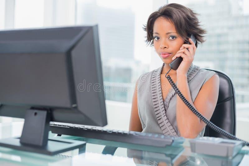 Серьезная коммерсантка говоря на телефоне пока смотрящ камеру стоковые фото