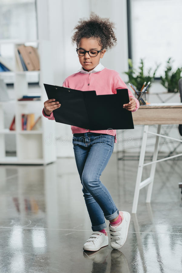 Серьезная маленькая девочка в eyeglasses держа доску сзажимом для бумаги и читая документы в офисе стоковое изображение rf