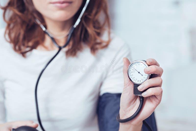 Серьезная молодая женщина демонстрируя индекс кровяного давления дома стоковое изображение