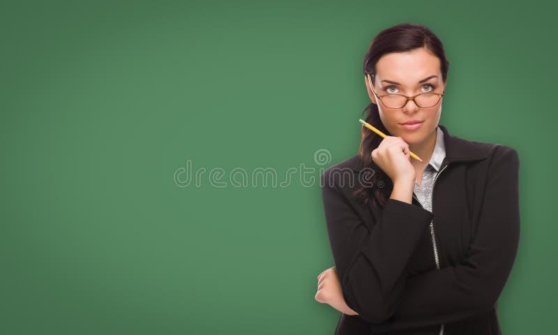 Серьезная молодая женщина с карандашем перед пустой доской мела стоковые изображения