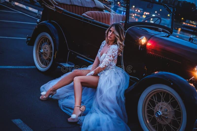 Серьезная невеста сидя на краю классического автомобиля с откидным верхом стоковая фотография rf