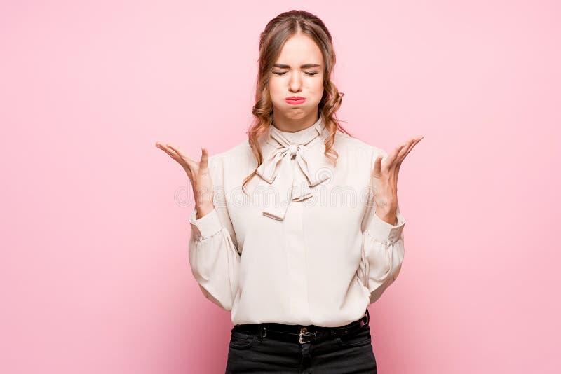 Серьезная разочарованная молодая красивая бизнес-леди на розовой предпосылке стоковые фотографии rf
