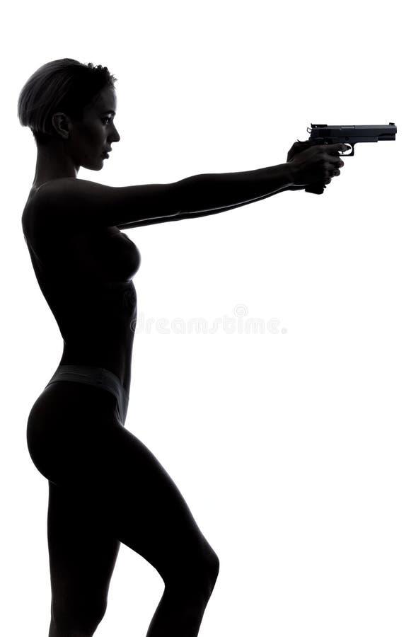 Серьезная уверенная девушка в стильном нижнем белье идя к снимать оружие стоковые изображения rf