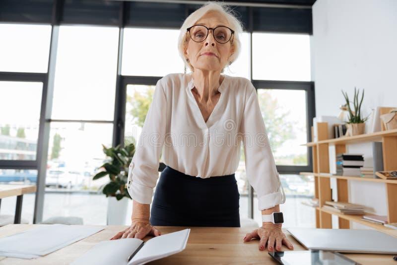 Серьезная умная склонность женщины на таблице стоковое фото rf