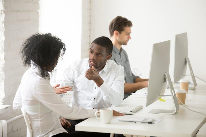 Серьезные Афро-американские коллеги говоря обсуждающ проект t стоковые изображения rf