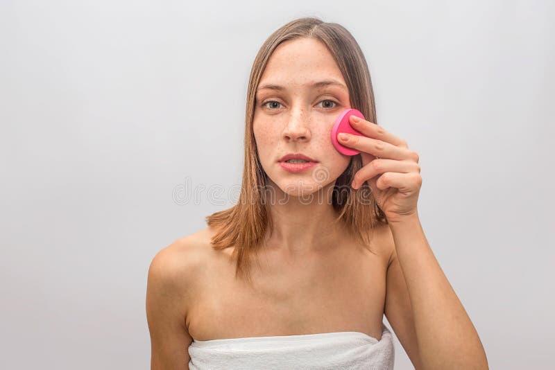 Серьезные и сконцентрированные взгляды молодой женщины на камере и делать процедуры по skincare Она использует розовую губку для  стоковые изображения