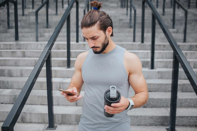 Серьезные и muscled стойки молодого человека на лестницах и взгляды на телефоне он hs в одной руке Черная бутылка в других стоковые фото