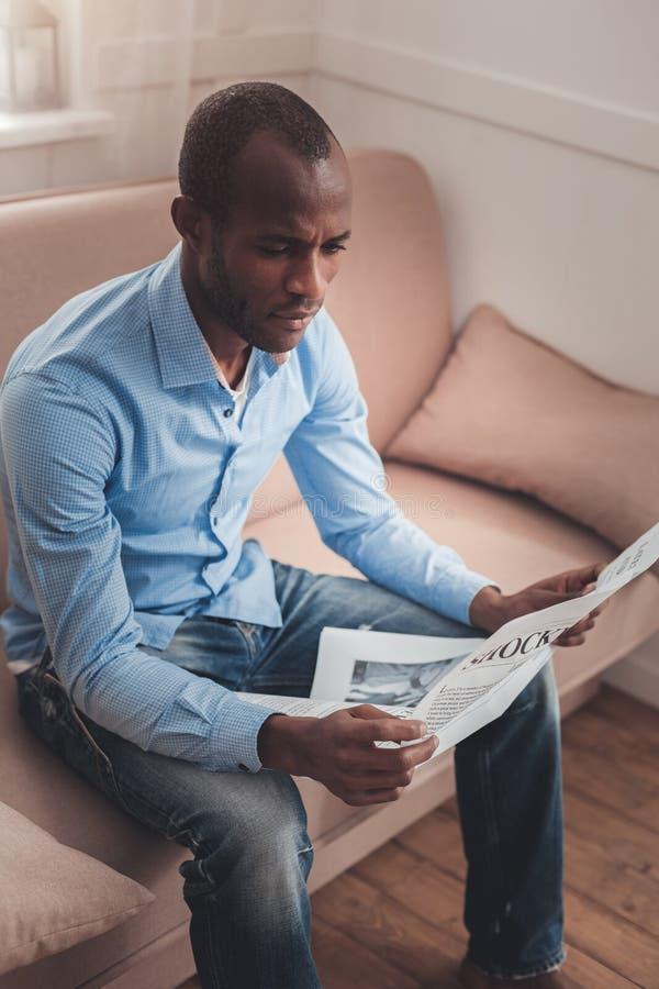 Серьезные новости молодого человека читая самые последние стоковое фото rf