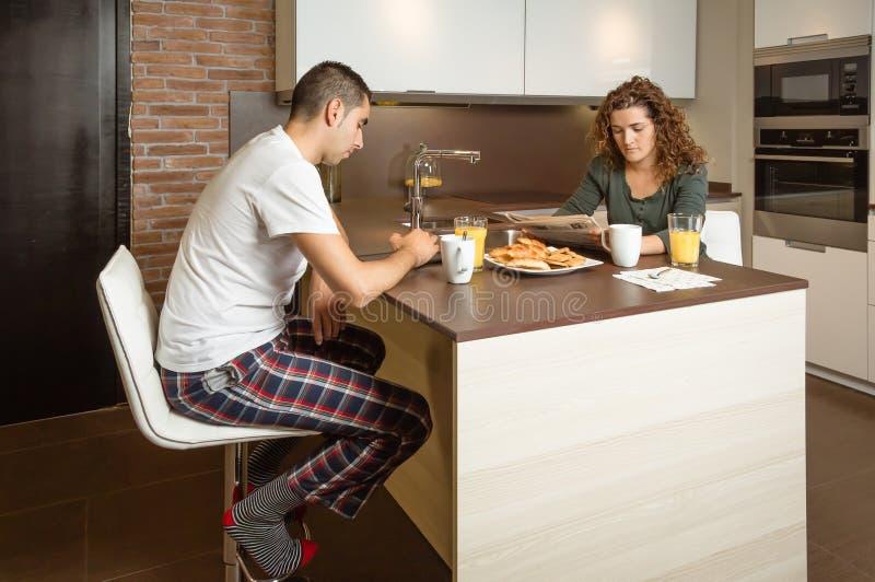 Серьезные новости чтения пар в домашнем завтраке стоковые изображения rf