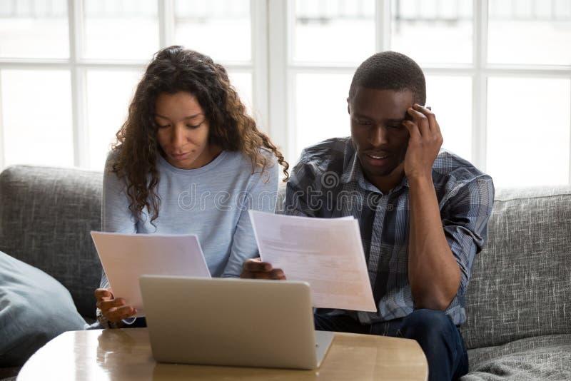 Серьезные обеспокоенные Афро-американские пары держа чтение счетов стоковое изображение