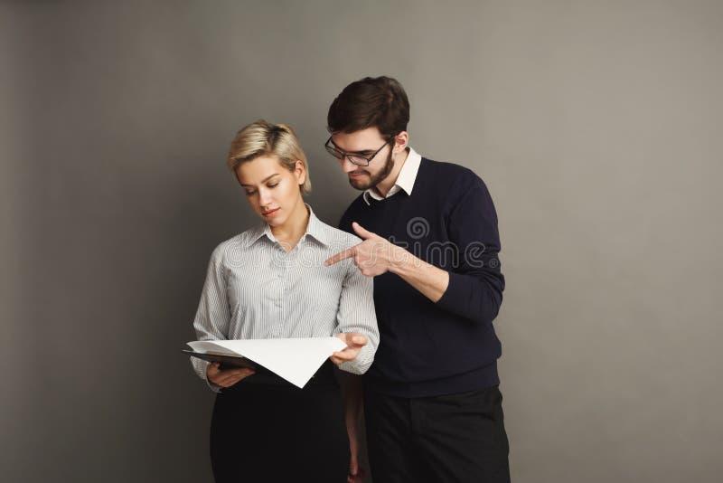 Серьезные пары в официально одеждах на серой предпосылке стоковые изображения rf