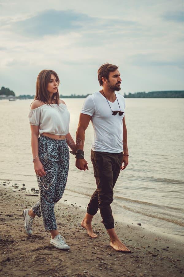 Серьезные пары держа руки пока идущ на пляж стоковые изображения
