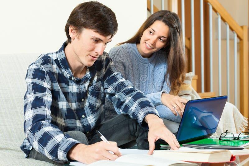 Серьезные студенты подготавливая для экзамена с книгами стоковое фото