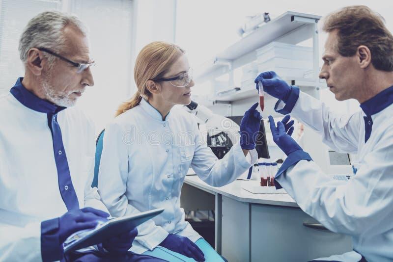 Серьезный ассистент лаборатории демонстрируя пробирку стоковое фото rf