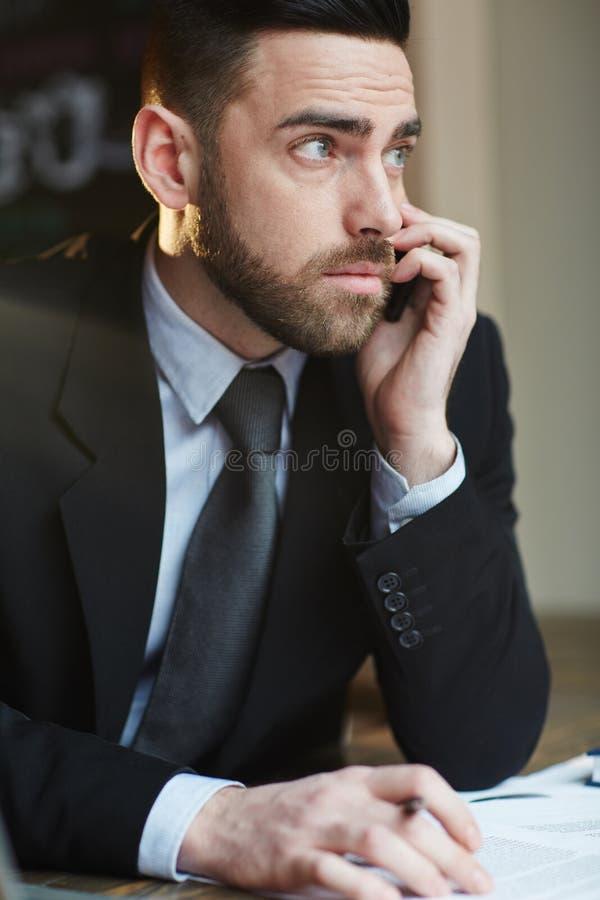 Серьезный бизнесмен говоря на телефоне в офисе стоковое фото rf
