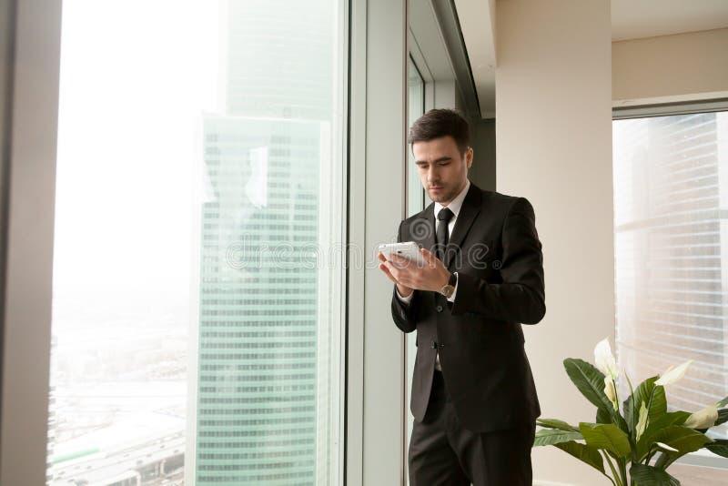 Серьезный бизнесмен держа таблетку стоя около большого окна в o стоковое фото rf