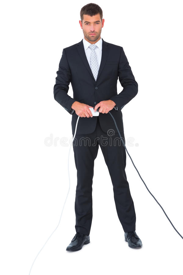 Серьезный бизнесмен соединяя штепсельную вилку стоковая фотография