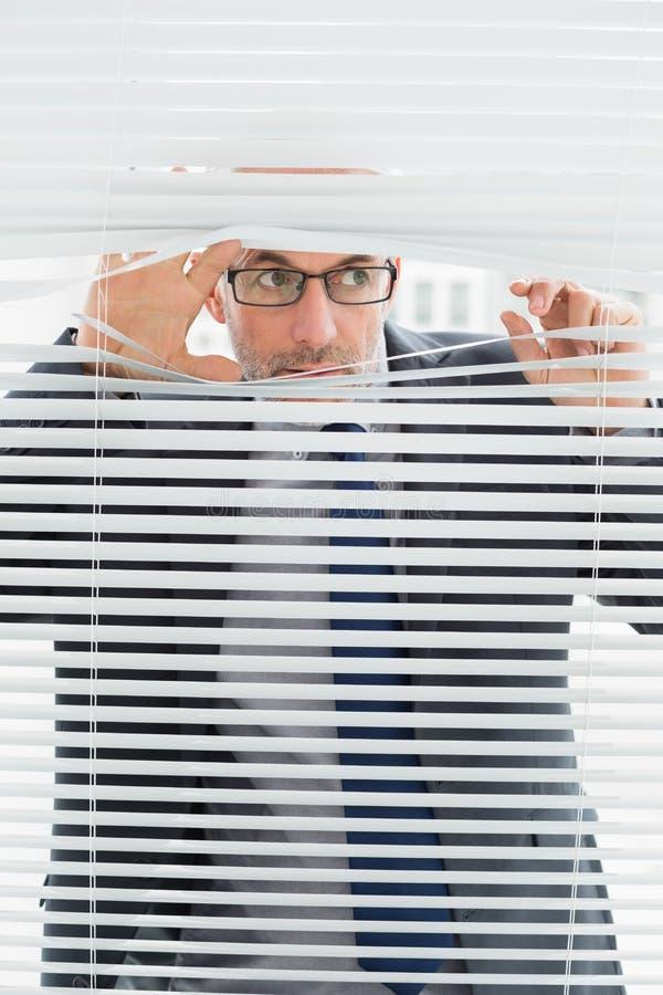 Серьезный бизнесмен peeking через шторки в офисе стоковое изображение