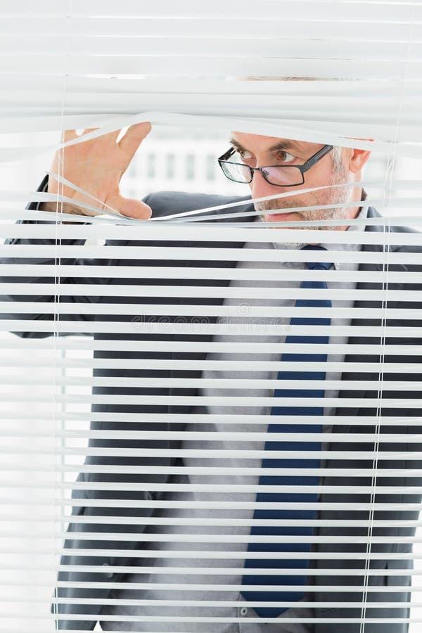 Серьезный бизнесмен peeking через шторки в офисе стоковое фото rf