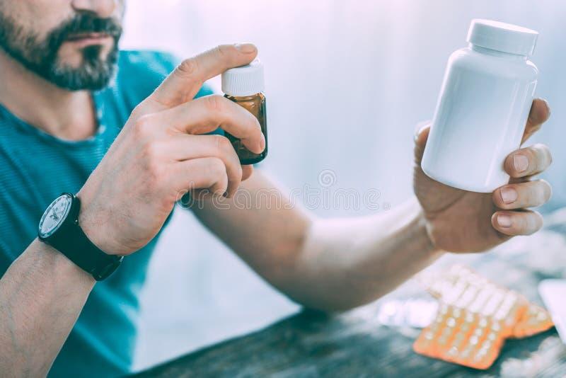 Серьезный больной бородатый человек выбирая некоторые таблетки стоковая фотография rf