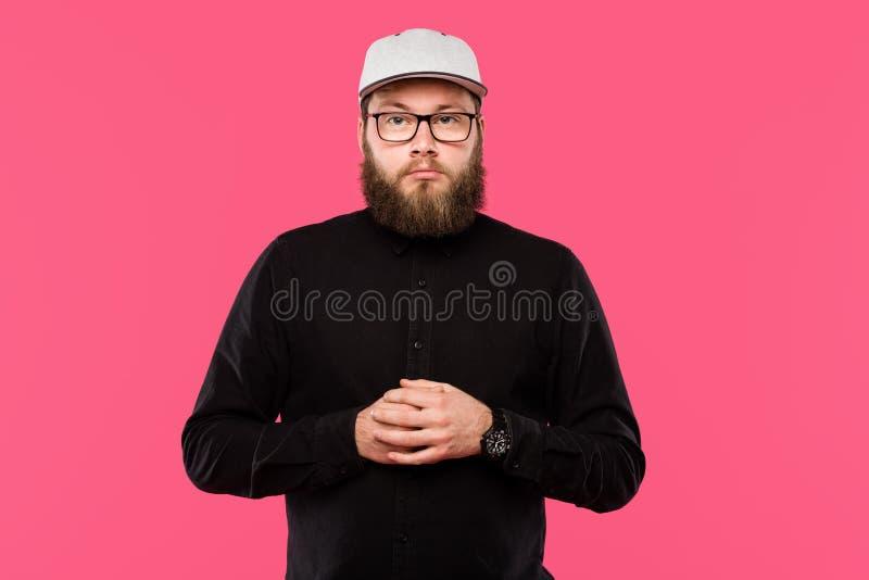 серьезный бородатый мужской хипстер в шляпе и eyeglasses крышки смотря изолированную камеру стоковые фотографии rf