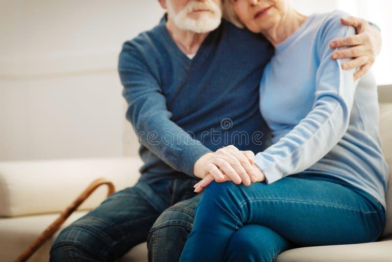 Серьезный бородатый человек обнимая его жену стоковое изображение