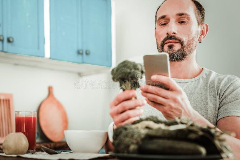 Серьезный бородатый человек смотря его экран смартфона стоковая фотография