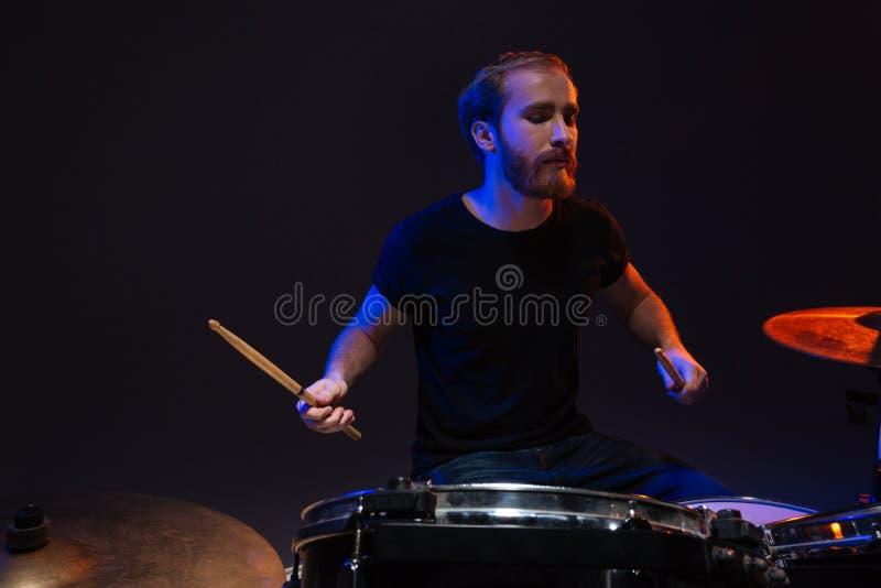 Серьезный бородатый мужской барабанщик играя барабанчики стоковое изображение