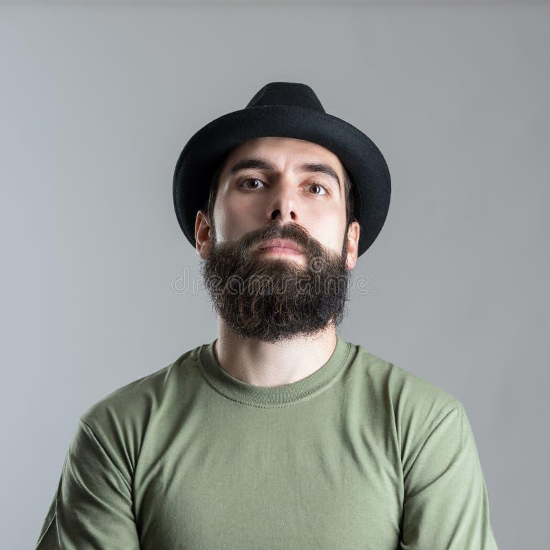 Серьезный грубый бородатый мачо человек смотря камеру стоковая фотография