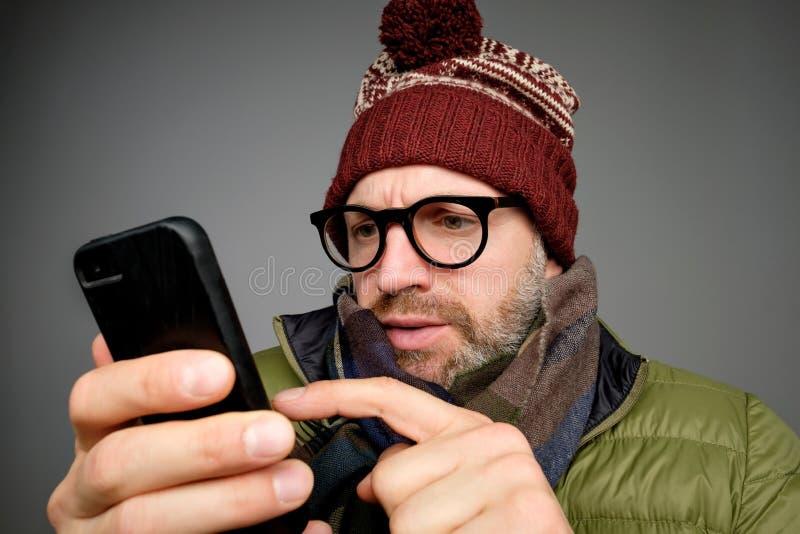 Серьезный зрелый человек в теплых одеждах и шляпе читая текстовое сообщение на его телефоне Sms с плохой новостью стоковое изображение