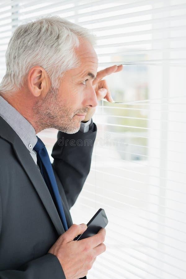 Серьезный зрелый бизнесмен peeking в офисе стоковое фото